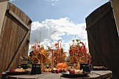 Bundles of straw decorated with flowers on set wooden table in front of open wooden gate with view of cloudy autumn sky