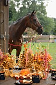 Bundles of straw decorated with flowers; horse in background