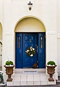 Christmas wreath hung on blue wooden panelled door with planted urns on front steps