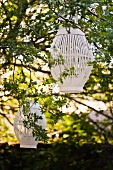 White slatted lanterns hanging in summery broad-leafed trees