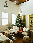 Wicker sofa set with white cushions below Art-Deco pendant lamps and Christmas tree in rustic living room