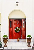 Christmas wreath on red panelled wooden door of villa with planted urns on front steps