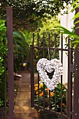 Herzförmiger Türkranz an geöffnetem Gartentor