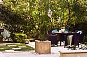 Gartenmöblierung und Pflanzenbehälter mit Zypresse auf gepflasterter Fläche in sonnigem Garten einer alten Villa