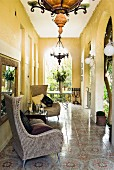 Yellow-painted veranda with arches, comfortable wicker armchairs and ornamental floor tiles