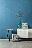 Vintage arrangement of old stool, metal locker, flowering branches in demijohn and DIY string art picture against blue-grey wall