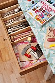 Rustic kitchen table covered in oilcloth with open cutlery drawer