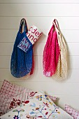 Net shopping bags of different colours hanging on white wall above embroidered scatter cushion