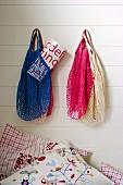 Veschiedenfarbige Netz Einkaufstaschen an weisser Holzwand aufgehängt, darunter besticktes Kissen