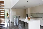 Open-plan, designer fitted kitchen with white counter and glossy stone floor in modern house