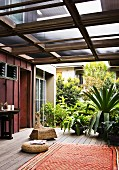 Ethnic rug and various rattan seats next to tropical, potted plants on roofed terrace