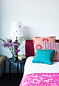 Stack of colourful scatter cushions on bed next to table lamp and vase of flowers on bedside table