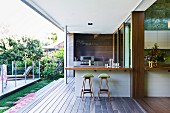 Bar counter and bar stools on veranda of modern house with view into garden