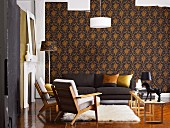 Living room with dark sofa, fifties-style armchairs and flokati rugs against elegant, dark patterned wallpaper