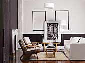 Living room with black-painted dado and modern artwork with lettering motif in front of empty picture frames behind seating group with pale upholstery
