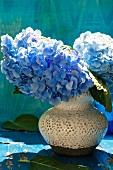 Pale blue hydrangeas in ceramic vase