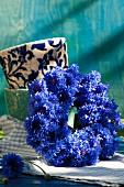Wreath of cornflowers leaning against stacked beakers