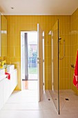 Yellow-tiled bathroom with washstand and floor-level shower with glass partition; view into garden through open door
