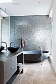 Designer bathroom with round bathtub against wall with grey, shimmering structure and washstand with anthracite basin