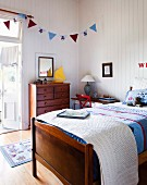 Bed with patchwork bedspread, bunting above wooden chest of drawers and white wood-panelling in cheerful, country-house, child's bedroom