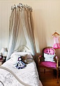 Rag doll on child's fairy-tale bed with crown-shaped canopy next to antique chair with deep pink upholstery