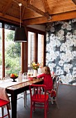 Red and white chairs at rustic wooden table, little girl kneeling on chair, floor-to-ceiling terrace doors and floral wallpaper on back wall