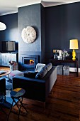 Modern sofa on rustic wooden floor and white African headdress above open fireplace in blue lounge