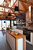 Narrow wooden counter with base cabinets in open-plan, high-ceilinged designer kitchen with black pendant lamps suspended from exposed roof structure