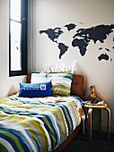 Teenager's bed with striped covers and Alva Aalto wooden stool below world-map stickers and name on wall