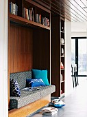 Wooden shelves with sofa in reading niche and textiles in shades of blue