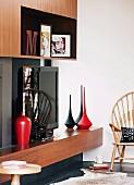 Extravagante, schwarze und rote Vasen in 70er Jahre Einbauregal mit Fernseher