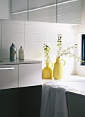 White wall tiles and sprigs of flowers in yellow retro vases and edge of bathtub in bathroom