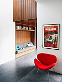 Framed vintage poster above retro armchair in front of custom shelving with integrated reading niche