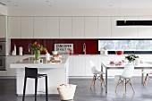 Offene, helle Küche mit langgestreckter Einbauzeile, Kücheninsel und Essplatz mit Eames Stühlen