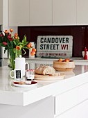 Breakfast place setting on island counter in front of vintage street sign on fitted kitchen counter