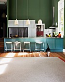 White rug in front of pale blue counter, bar stools, pendant lamps and green-painted wall in open-plan kitchen