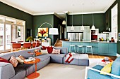 Sofa combination, dining area and kitchen counter in open-plan interior with green wall