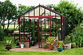 Planters in and around greenhouse in rural setting