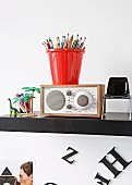 Buntstifte in rotem Behälter auf Radio zwischen Miniatur Stuhl und Spielzeug auf schwarzem Regal an Wand