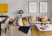 Elegant sofa set with gold scatter cushions and modern coffee table in living room painted pale grey with dining set to one side