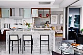 Elegant designer interior with open-plan kitchen, bar stools with black wooden frames and marble counter
