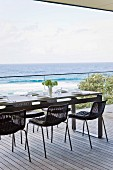 Black mesh chairs around set table on wooden deck with panoramic view of Pacific Ocean