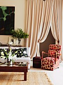Elegant armchair with red and white floral cover in front of draped, floor-length curtains in traditional interior