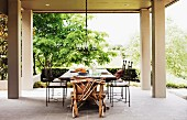 Rustic chair made from branches and delicate metal chairs around table on spacious roofed terrace with garden view