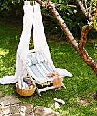 Rustic deckchair with striped seat under white fabric canopy hanging from tree in garden