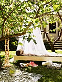 Shady spot in garden - airy canopy above wicker day bed behind picnic blanket and cushions on lawn