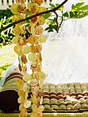 Relaxation spot in summery garden - strings of shells hung from tree in front of striped futon on lawn