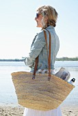 Blonde woman with woven picnic bag on beach