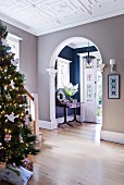 Christmas tree in hall with large, arched open doorway and view into vestibule of traditional house