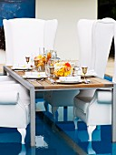 Festively set table and throne-like, white, upholstered armchairs on special floor insert in swimming pool
